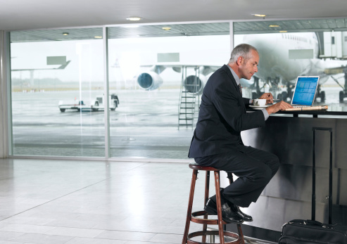 Mature businessman reading newspaper by laptop in airport, side view